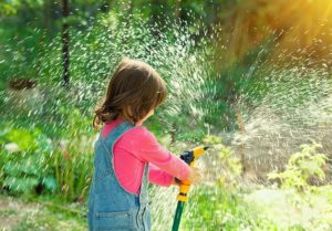 Girl spraying garden hose