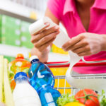 Start your food budget makeover. Woman with grocery receipt at cart