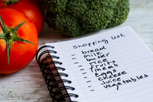 Grocery list near vegetables. Grocery shopping mistakes