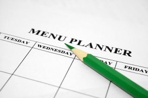 Menu planner calendar with green pencil. Meal planning for beginners