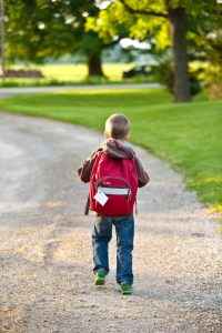 Backview of boy in backpack. Budget for school clothes now.