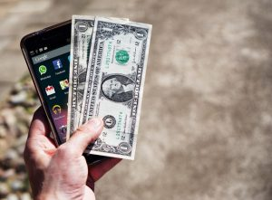 Person holding cash and cell phone