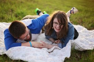 Affectionate man and woman smiling on picnic blanket. Date night ideas