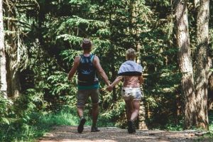 Man and woman walking in forest.