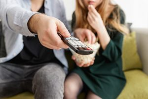 Man holding remote and eating popcorn with woman