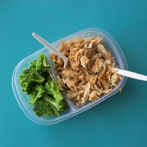 Chicken, rice and broccoli in a plastic container. How to avoid buying lunch at work