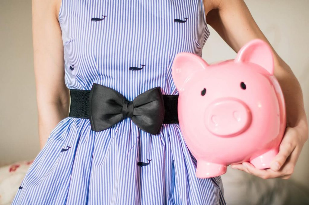 Woman in blue dress holding piggy bank. Budget tips for beginners