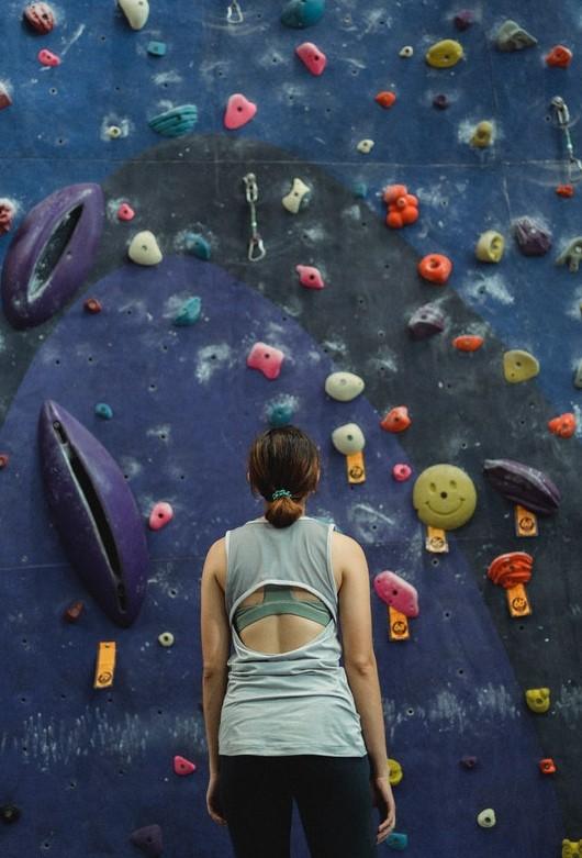Woman staring up at climbing wall